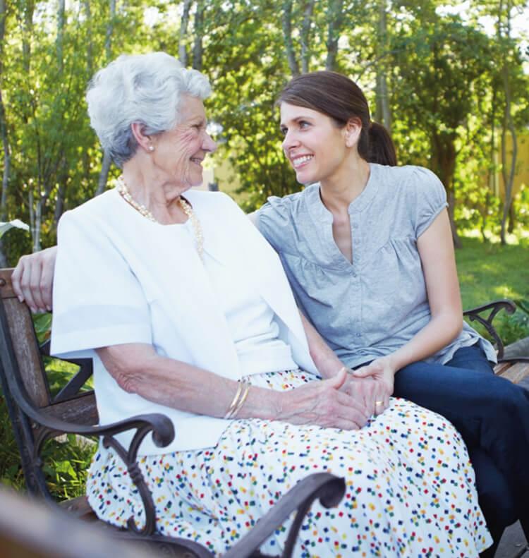 Eine Frau und eine alte Dame sitzen draußen auf einer Bank