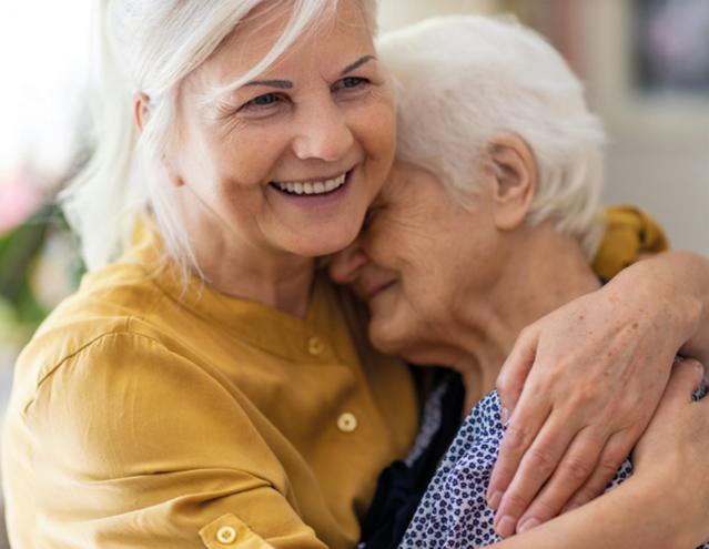 Zwei ältere Damen liegen sich im Arm