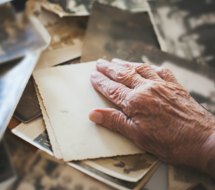 Eine Hand von einem alten Mann ruht auf Bildern von früher